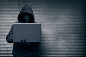 Hooded hacker with mask holding laptop while typing against metal roller shutter door background