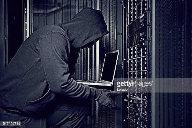 Hooded male hacker using laptop in server room