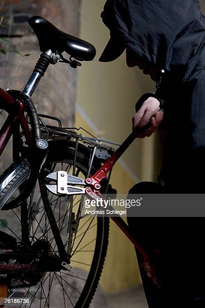 A hooded man cutting a bicycle lock with bolt cutters