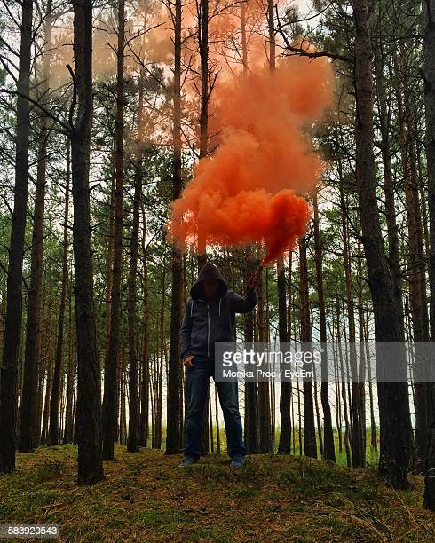 Hooded Man Holding Distress Flare Against Trees On Field
