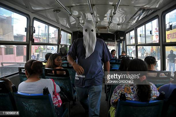 A hooded man looks for members of the Salvatrucha gang on board of a bus in Castanas neighborhood in the southern outskirts of Guatemala City on July...