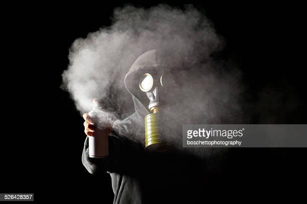 Con cappuccio uomo indossando Maschera antigas Spruzzare con Spray Can