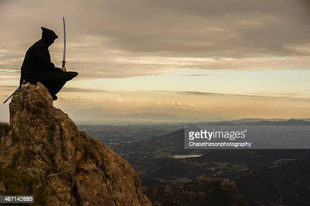 Hooded ninja with sword atop mountain peak
