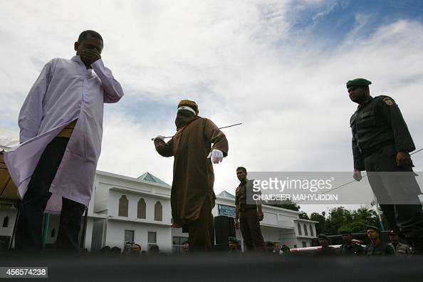 A hooded official canes a man for gambling at a public square in Banda Aceh on October 3 2014 Aceh is the only part of the world's biggest...