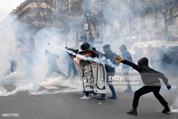 TOPSHOT Hooded participants throw back tear gas canisters as they clash with police within a demonstration called by the families of the victims of...
