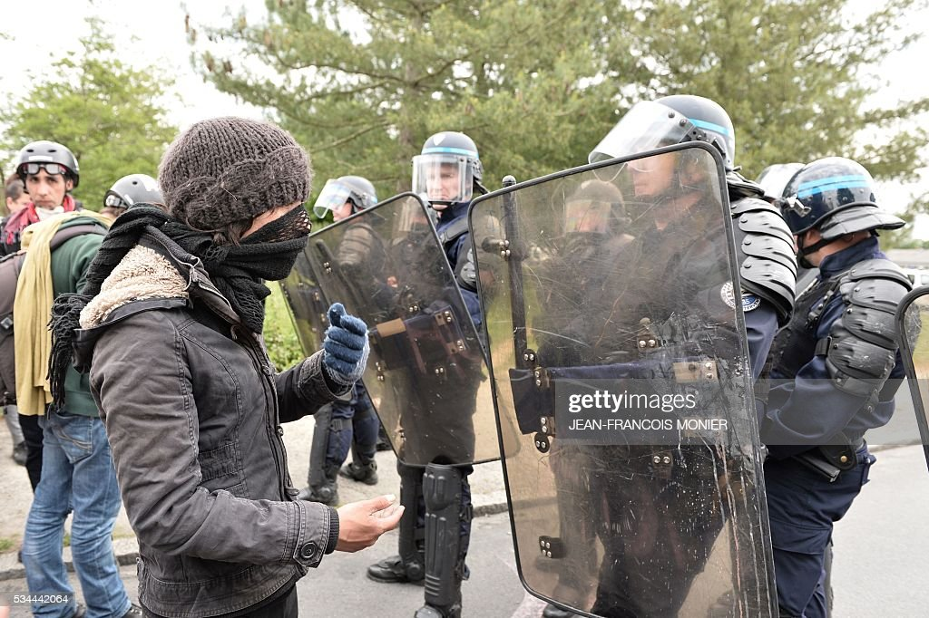 A hooded person stands in front of France's riot police members during a protest against the government's labour law reforms in Rennes, on May 26, 2016. The French government's labour market proposals, which are designed to make it easier for companies to hire and fire, have sparked a series of nationwide protests and strikes over the past three months. Masked youths clashed with police and striking workers blockaded refineries and nuclear power stations on May 26 as an escalating wave of industrial action against labour reforms rocked France. / AFP / JEAN