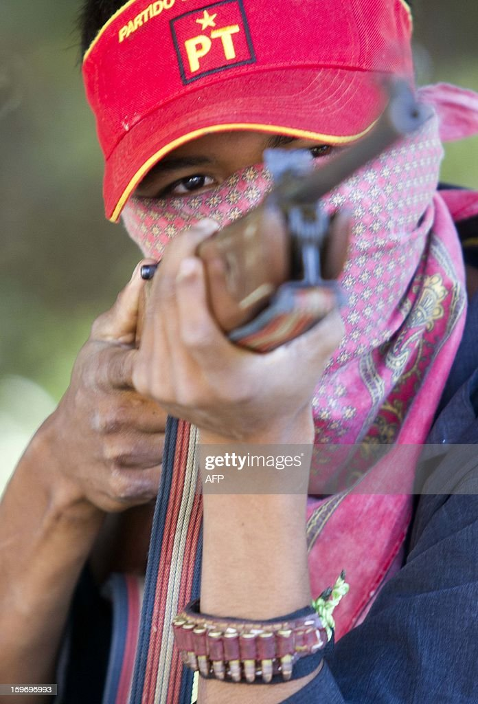 A hooded resident of Tecoanapa, in the Mexican southern state of Guerrero, forming their own vigilante police forces, stands guard at a checkpoint in the main access to the nearby village of Pericon on January 18, 2013. Hundreds of civilians armed with rifles, pistols and machetes decided to provide security for the communities of Tecoanapa and Ayutla de los Libre in the state of Guerrero, saying gangs were committing robberies, kidnappings and murder. The vigilante force has put up checkpoints on roads and conducts night watches in the towns. Guerrero, home to the Pacific resort town of Acapulco, has been one of the states hardest hit by Mexico's drug violence, which has left more than 70,000 people killed across the country since 2006. AFP PHOTO/Pedro Pardo