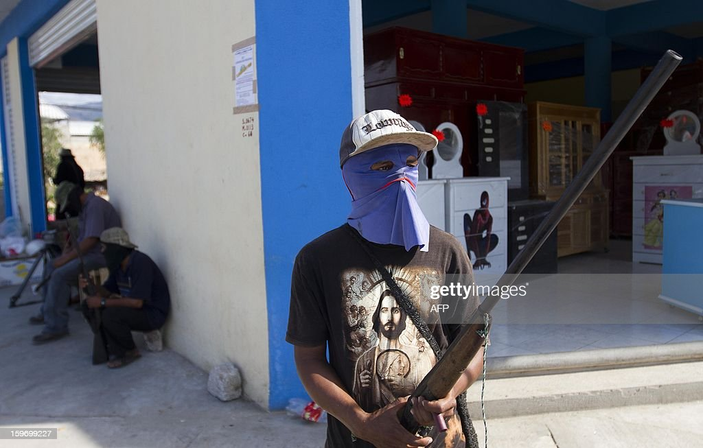 Hooded residents of Ayutla de los Libres, in the Mexican southern state of Guerrero, forming their own vigilante police forces, stand guard at a checkpoint in town, on January 18, 2013. Hundreds of civilians armed with rifles, pistols and machetes decided to provide security for the communities of Tecoanapa and Ayutla de los Libre in the state of Guerrero, saying gangs were committing robberies, kidnappings and murder. The vigilante force has put up checkpoints on roads and conducts night watches in the towns. Guerrero, home to the Pacific resort town of Acapulco, has been one of the states hardest hit by Mexico's drug violence, which has left more than 70,000 people killed across the country since 2006. AFP PHOTO/Pedro Pardo