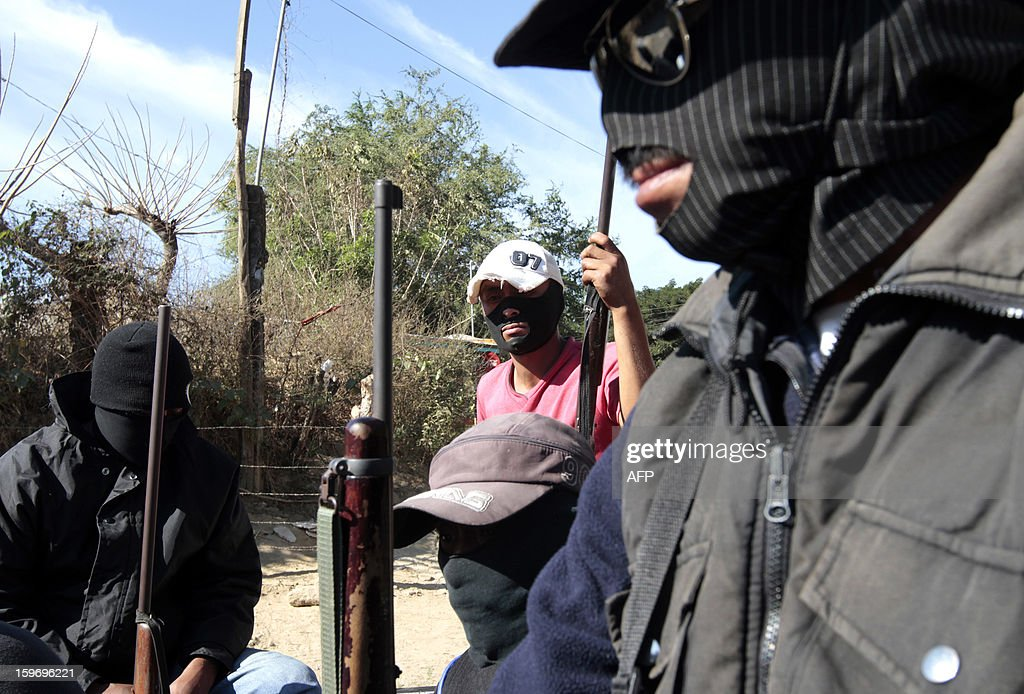 Hooded residents of Tecoanapa, in the Mexican southern state of Guerrero, forming their own vigilante police forces, stand guard at a checkpoint in the main access to the nearby village of Pericon on January 18, 2013. Hundreds of civilians armed with rifles, pistols and machetes decided to provide security for the communities of Tecoanapa and Ayutla de los Libre in the state of Guerrero, saying gangs were committing robberies, kidnappings and murder. The vigilante force has put up checkpoints on roads and conducts night watches in the towns. Guerrero, home to the Pacific resort town of Acapulco, has been one of the states hardest hit by Mexico's drug violence, which has left more than 70,000 people killed across the country since 2006. AFP PHOTO/Pedro Pardo