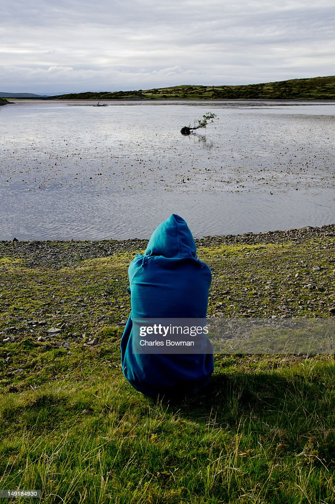 Hooded teenager looks to Welsh lake crooked tree : Stock Photo