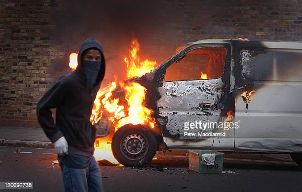 A hooded youth walks past a burning vehicle in Hackney on August 8 2011 in London England Pockets of rioting and looting continues to take place in...