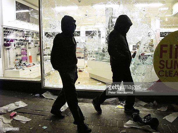 Hooded youths walk past a looted Debenhams store in Clapham Junction on August 8 2011 in London England Sporadic looting and clashes with police...