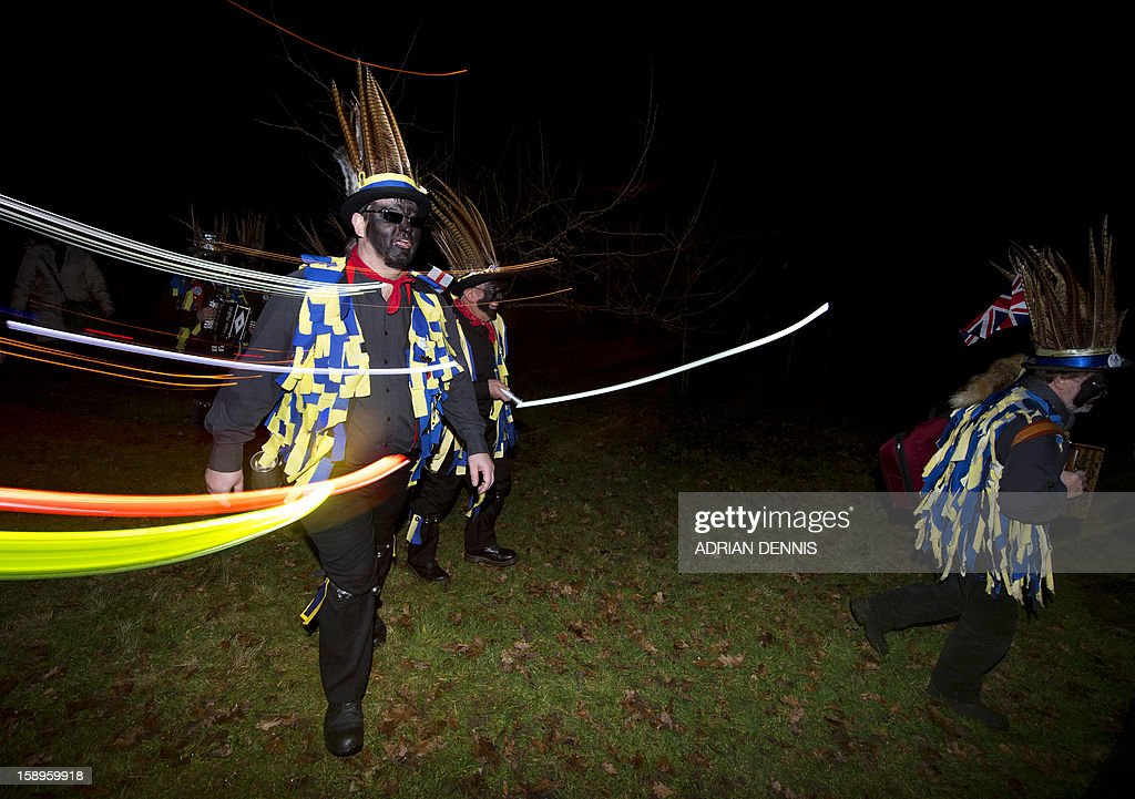 Hook Eagle Morris Men make their way through an orchard to toast the fruit trees in the orchard during the annual Wassail night in Hartley Wintney, 40 miles (64 Kilometers) west of London, on January 4, 2013. The event, held near to twelfth night, celebrates both the passing of Christmas and the future good health of the fruit trees. Traditionally the custom involved the local farm workers visiting the orchard after dark with shotguns, horns, food and a large pail of cider. They would make a loud noise to raise the Sleeping Tree Spirit and to scare off demons. Cider would be poured over the roots and pieces of toast placed in the branches as a gift to the spirit of the tree. The wassail song is sung as a blessing or charm to bring fruitfulness or even in admonishment not to fail in the upcoming year. AFP PHOTO / ADRIAN DENNIS