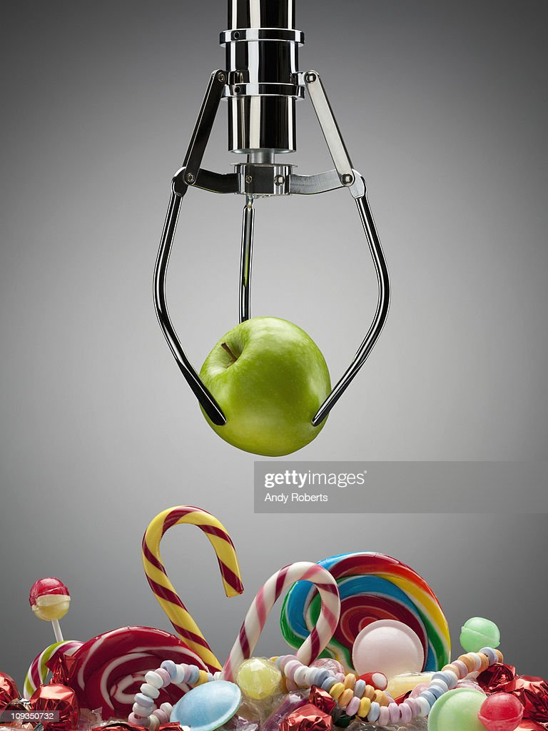 Hook with green apple above variety of sweet candies : Stock Photo