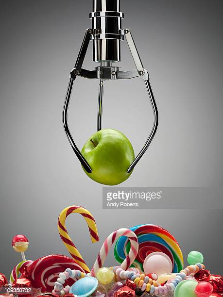 Hook with green apple above variety of sweet candies