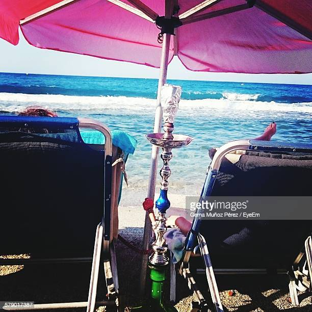 Hookah By Deck Chairs On Beach Against Sky