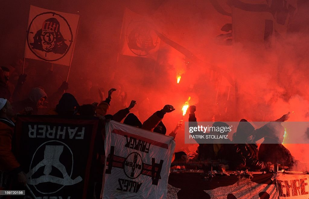 Hooligans hold flares during the German first division Bundesliga football match Bayer Leverkusen vs Eintracht Frankfurt in the German city of Leverkusen on January 19, 2013.