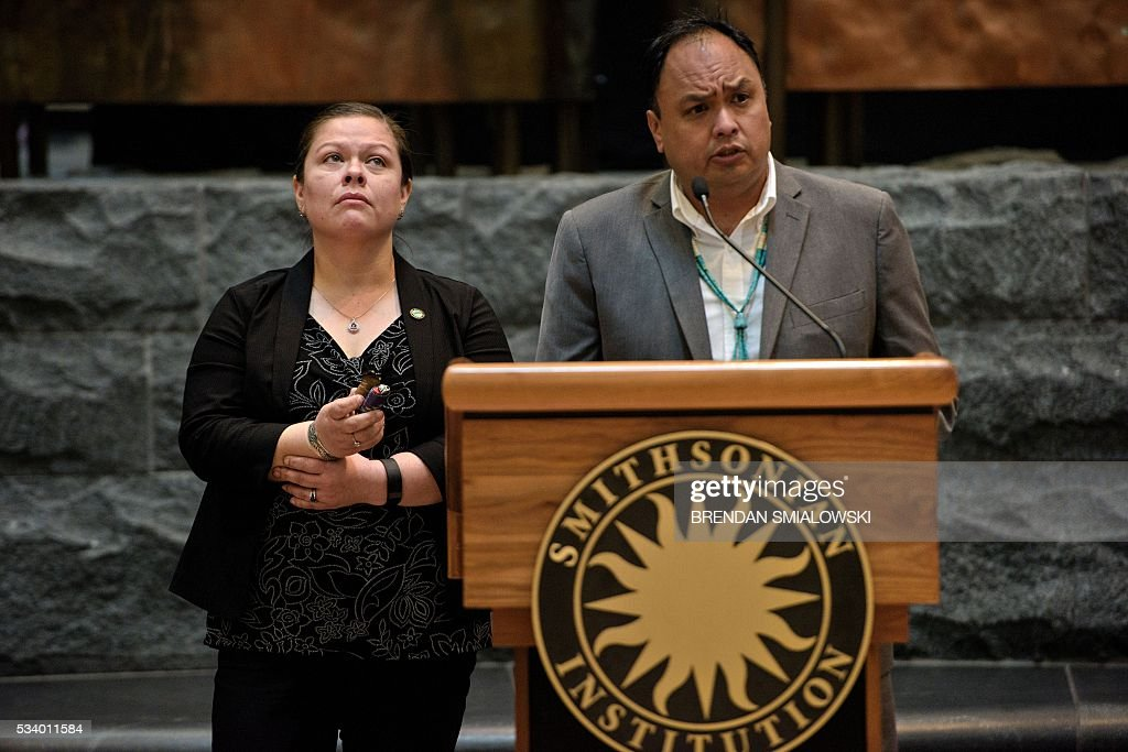 Hoopa Valley Tribal Council District Representative Leilani Pole (L) listens as Hoopa Valley Tribal Council District Representative Bradley Marshall speaks during an event at the Smithsonian National Museum of the American Indian to challenge the sale of American Indian artifacts and remains in France, May 24, 2016 in Washington, DC. In an international battle stretching from Native American lands in the American West to the auction houses of Paris, two tribes on May 24, renewed a years-long campaign to prevent the sale of sacred objects. The Acoma Pueblo Nation located in New Mexico and The Hoopa Valley Tribal Nation of California have announced their opposition to a scheduled sale next week of close to 500 artifacts at Paris' EVE auction house. / AFP / Brendan Smialowski