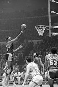 Los Angeles Lakers' Wilt Chamberlain looks like he's tiptoeing across thin air as he prepares to flip the ball through the hoop against the New York...
