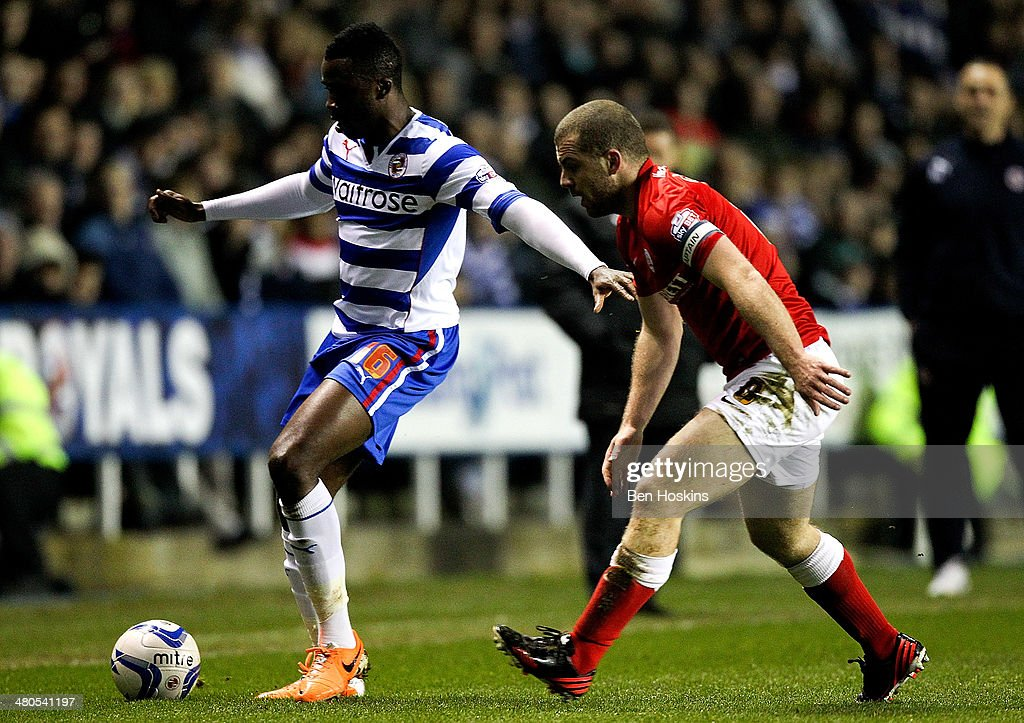 Hope Akpan of Reading holds off pressure from Stephen Dawson of Barnsley during the Sky Bet Championship match between Reading and Barnsley at Madejski Stadium on March 25, 2014 in Reading, England,