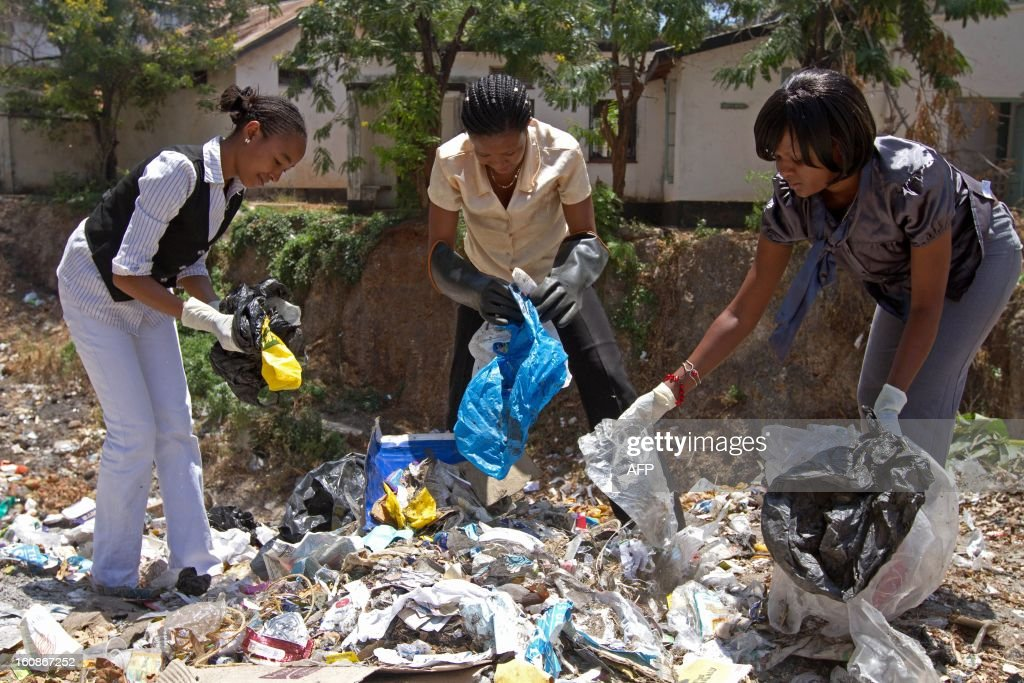 Hope Mwanyuma (C), latest United Nations Enivornmental Program (UNEP) Young Environmental Leader winner and two of her university collegues, pick out polythene bags from a dump site near the Old Town of Mombasa on February 5, 2013. Hope started a polythene recycling scheme turning discarded plastic bags into handbags, table mats and other accessories to try and reduce the huge amount of plastic bags that get used and discarded daily in Kenya.