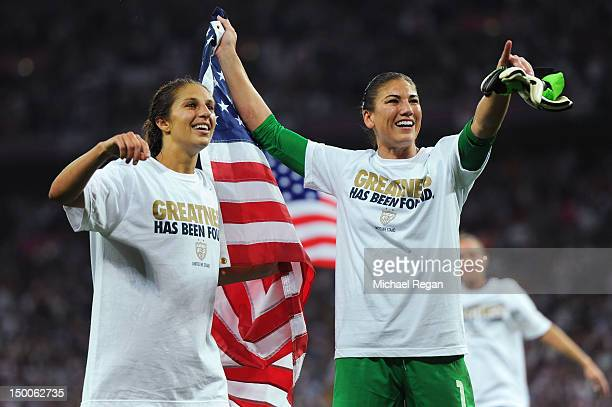 Hope Solo and Carli Lloyd of the United States celebrate with the American flag after defeating Japan by a score of 21 to win the Women's Football...