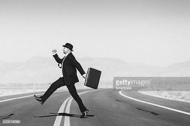 Hopeful businessman with suitcase crossing the road