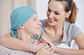 Hopeful cancer woman wearing headscarf, talking with friend