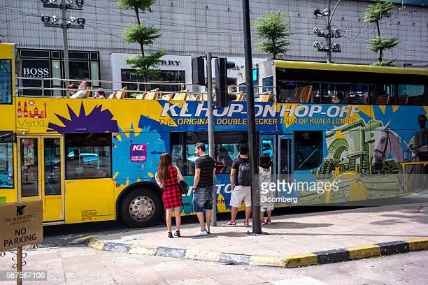 A hopon hopoff bus passes pedestrians in the Bukit Bintang area of Kuala Lumpur Malaysia on Friday Aug 5 2016 Malaysia's secondquarter gross domestic...