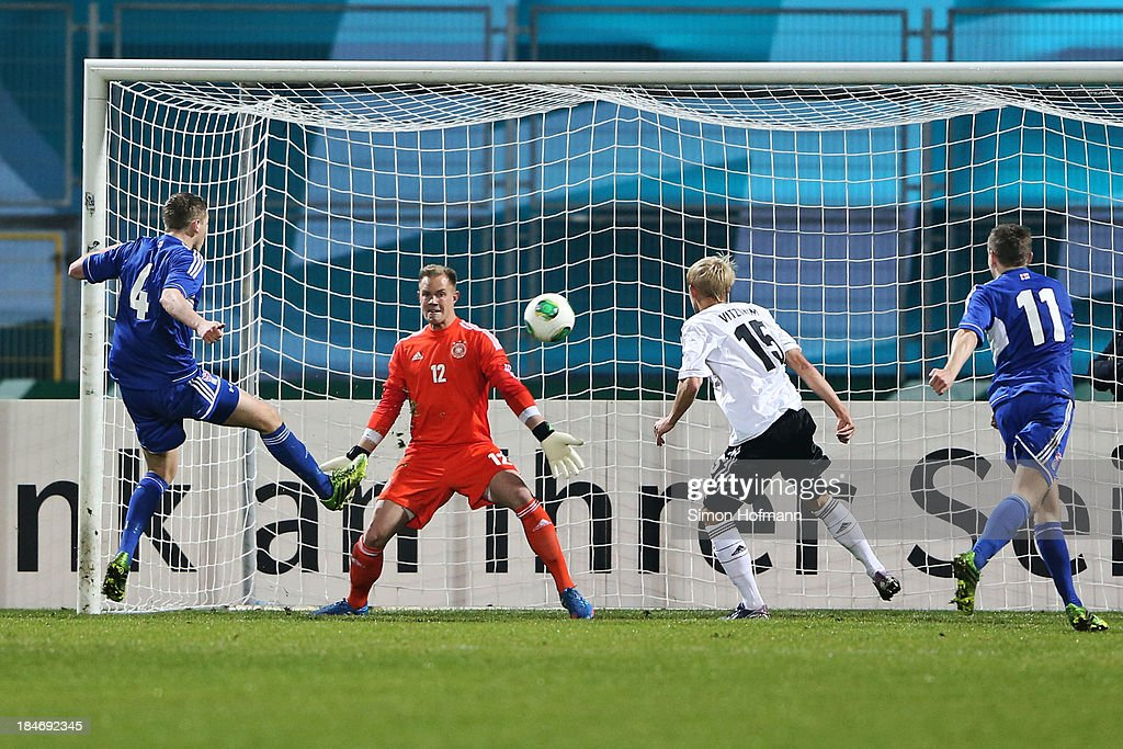 Hordur Askham of Faroe Islands (L) scores his team's second goal against goalkeeper <a gi-track='captionPersonalityLinkClicked' href=/galleries/search?phrase=Marc-Andre+ter+Stegen&family=editorial&specificpeople=5528638 ng-click='$event.stopPropagation()'>Marc-Andre ter Stegen</a> of Germany during the 2015 UEFA European U21 Championships Qualifying Group Six match between Germany U21 and Faroe Islands U21 at Auestadion on October 15, 2013 in Kassel, Germany.