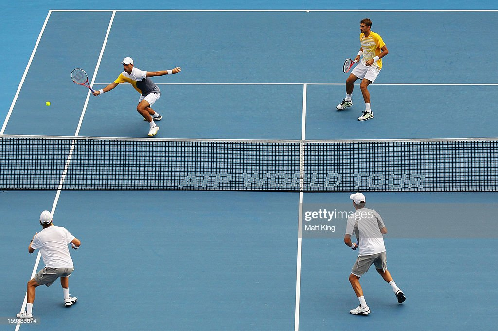 Horia Tecau of Romania (L) plays a volley at the net playing with Max Mirnyi of Belarus against Bob Bryan and Mike Bryan of USA during day seven of the Sydney International at Sydney Olympic Park Tennis Centre on January 12, 2013 in Sydney, Australia.