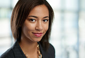 Portrait of a confident young mixed-raced female employee part of a business team. Serie shot with a pastel, out of focus glass window background.