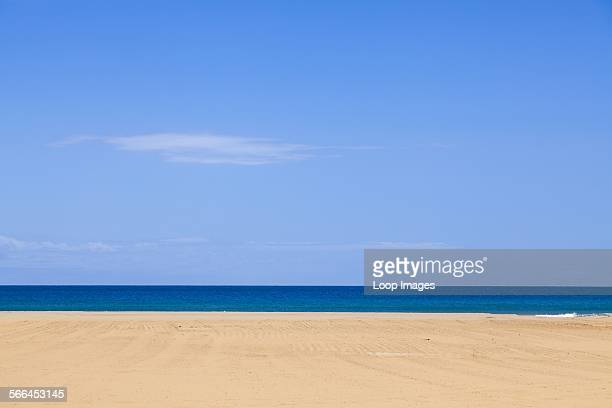 Horizontal lines of sandy beach with blue sea and sky