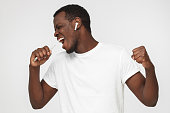 Horizontal photo of young African American man pictured isolated on gray background enjoying music through wireless earphones so much that he is dancing with closed eyes, energetic and full of joy