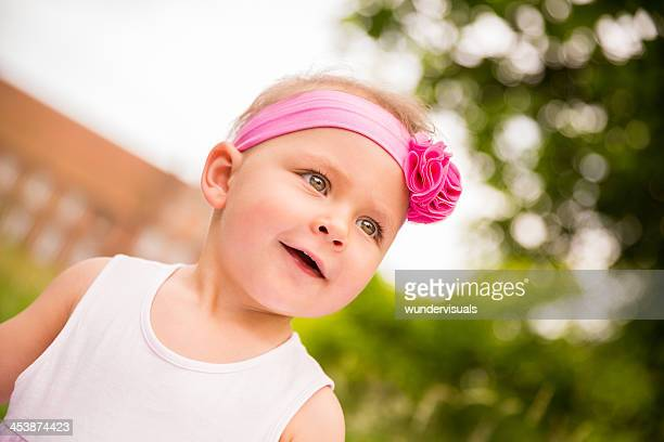 Horizontal portrait of baby girl in pink smiling