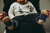Little male toddler sitting on mother's laps, wearing casual clothing, without faces, family portrait