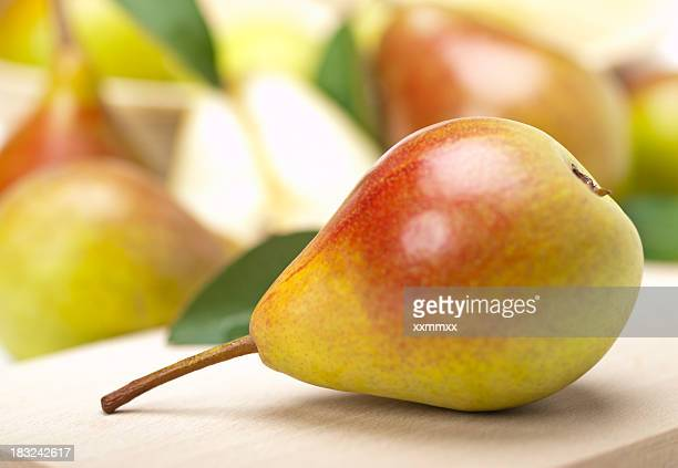 A horizontal ripe pear in front of several other pears