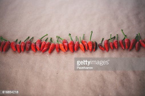 Horizontal row of hot spicy red Thai chili peppers. : Stock Photo