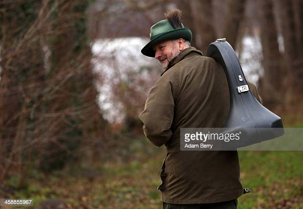 A horn player with a traditional German hunter's cap walks next to the Obersee lake in Lanke about 50 kilometers north of Berlin on December 22 2013...