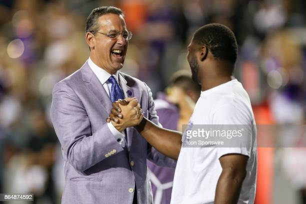 Horned Frogs Athletic Director Chris Del Conte shakes hands with former TCU and NFL player LaDainian Tomlinson during a ceremony at the game between...