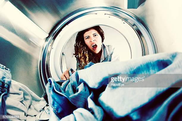 Horrifié jeune femme en vêtements à la blanchisserie grimaces au sec.