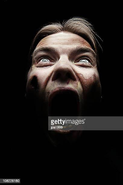 A horror image of a female covered in blood screaming
