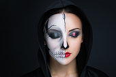 woman monster. Creative dark make-up, conceptual idea for Halloween. Eerie nightmare turning into a black vampire, volume spikes body art painting. Professional photo darkness background horizontal