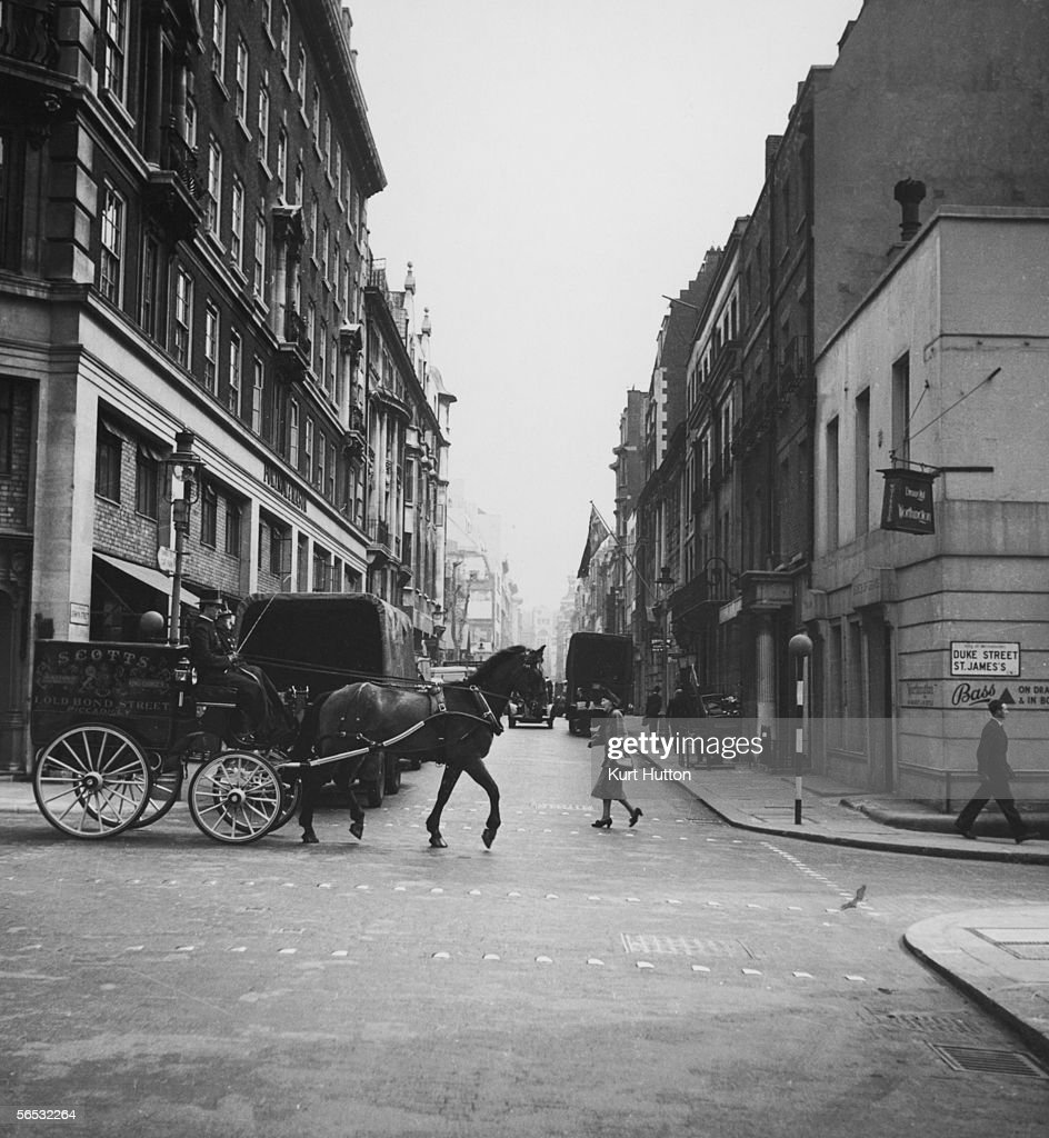A horse and cart advertising the hat shop Scott's passes the junction of Duke Street and Jermyn Street London May 1951 Original publication Picture...