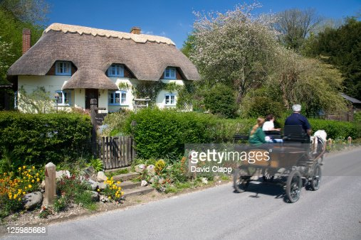 Horse and cart passing cottage in Wherwell, Hampshire, England : Stock Photo