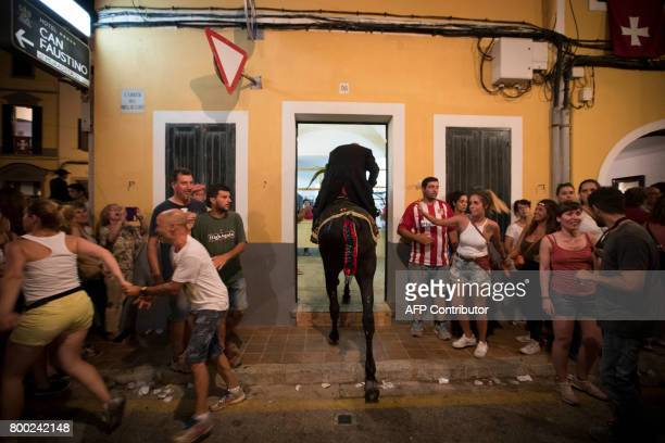A horse and his rider enter a house during the traditional San Juan festival in the town of Ciutadella on the Balearic Island of Menorca in the night...