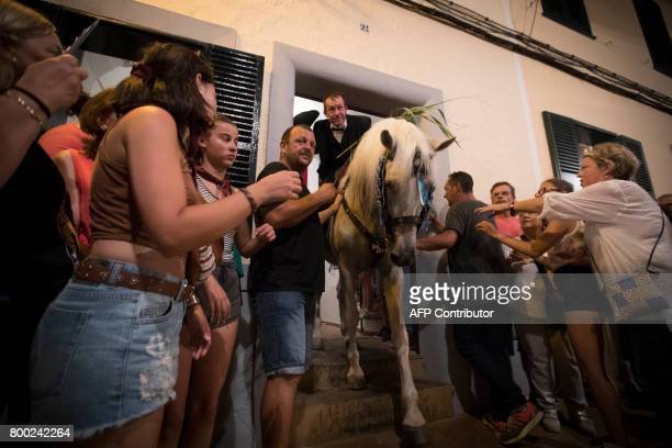A horse and his rider leave a house during the traditional San Juan festival in the town of Ciutadella on the Balearic Island of Menorca in the night...