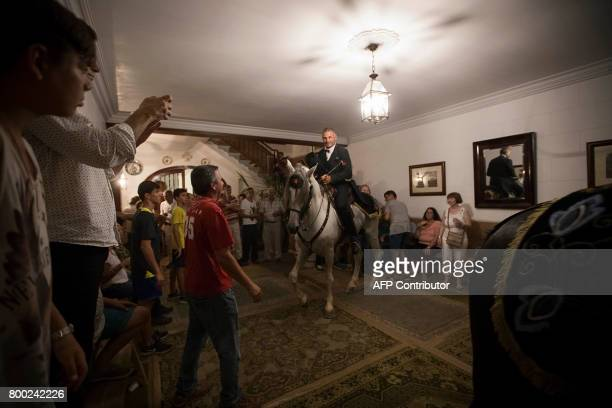 A horse and his rider walk inside a house during the traditional San Juan festival in the town of Ciutadella on the Balearic Island of Menorca in the...