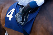 The unity of thoroughbred horse and jockey on the way down to the start at the racecourse. Close up of jockey's riding boot, saddle and number 4 saddle cloth on a bay thoroughbred racehorse.