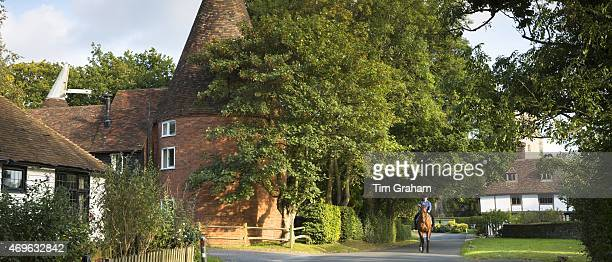 Horse and rider in quaint attractive village of Smarden with traditional Kentish oast house in High Weald in Kent England UK